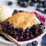 blueberry cobbler on small plate served with a scoop of vanilla ice cream. Fresh blueberries scattered about.