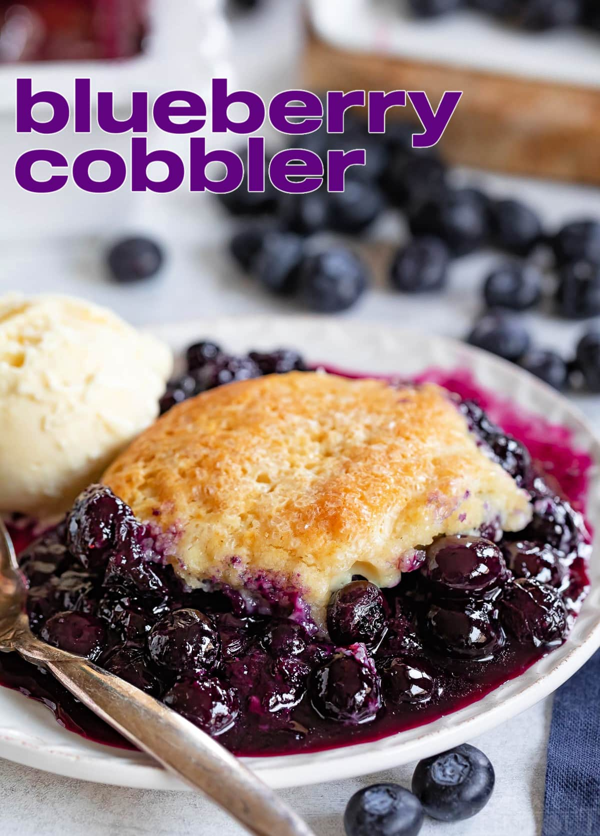 blueberry cobbler on small plate served with a scoop of vanilla ice cream. Fresh blueberries scattered about. Title overlay at top of image.