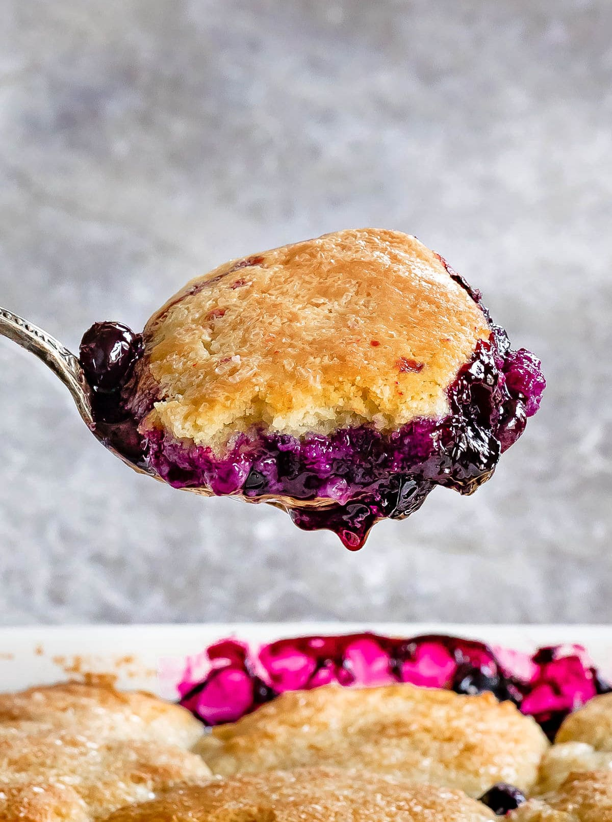 a scoop of blueberry cobbler held up over baking dish.