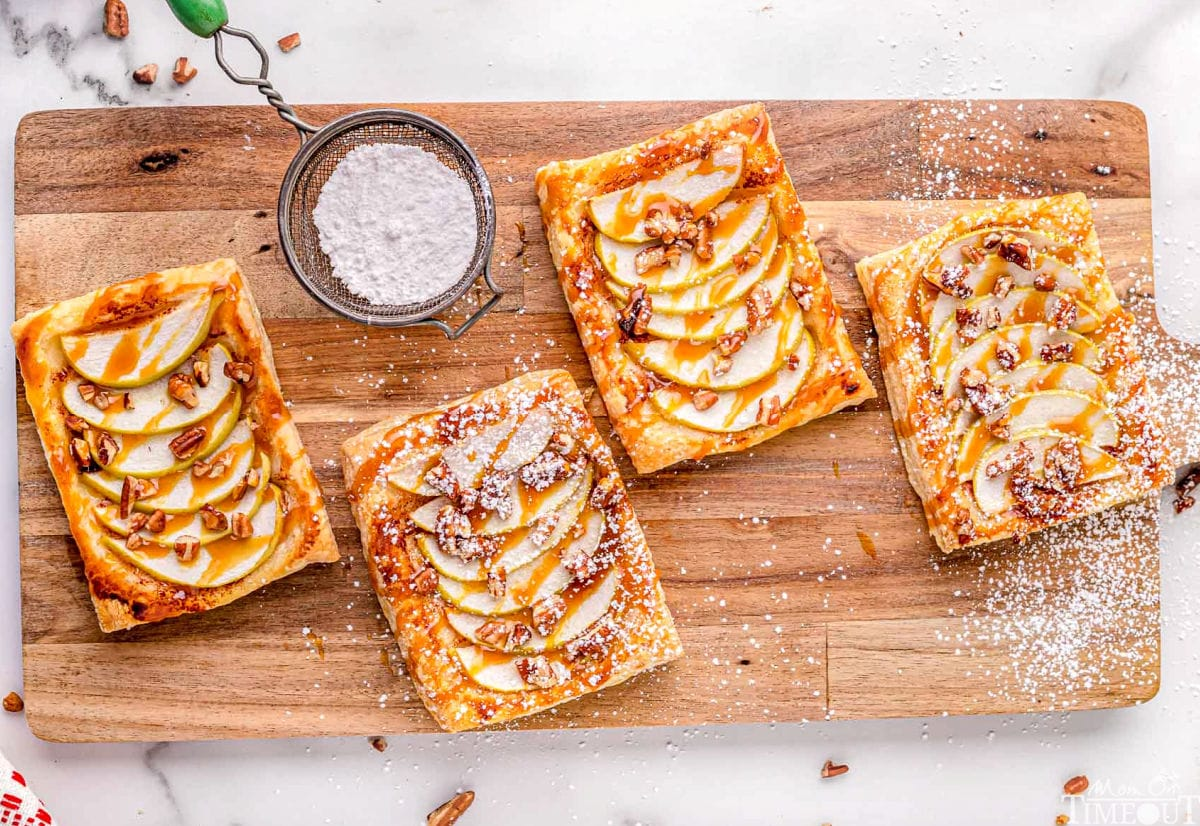 four apple tarts sitting on large wood cutting board drizzled with caramel and sprinkled with powdered sugar.