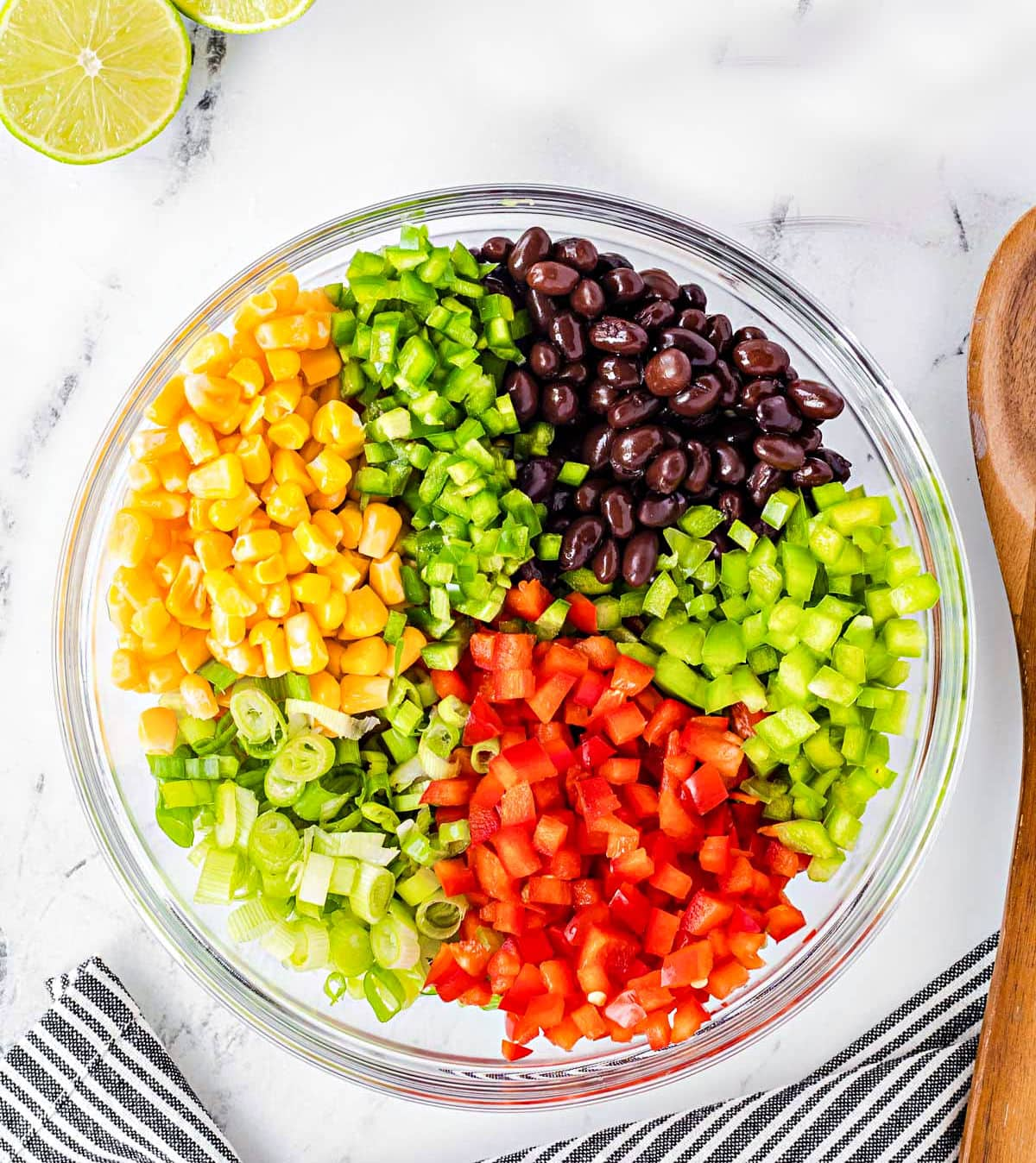 black bean corn salsa ingredients prepped and in a clear glass bowl ready to be mixed together.