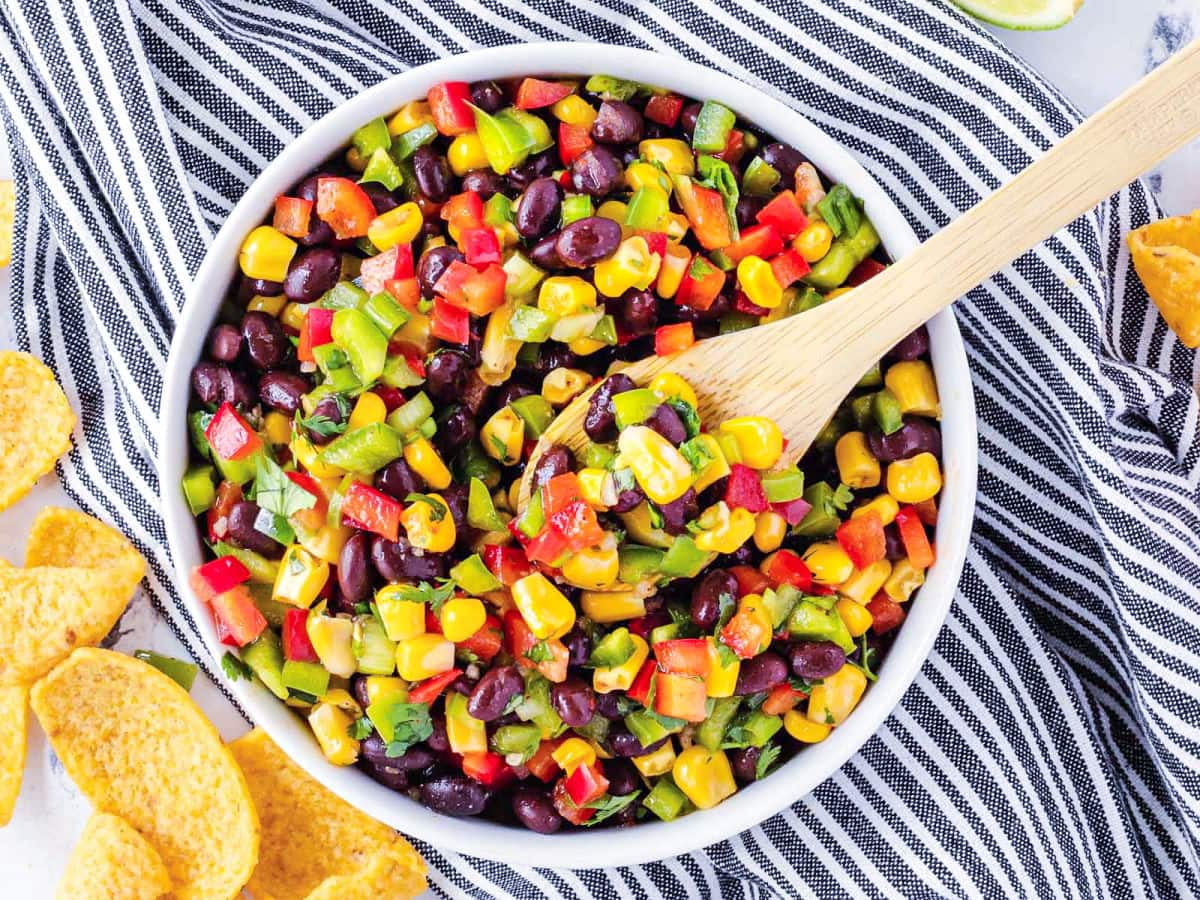 corn bean salsa in white bowl with wood serving spoon. bowl sitting on a black and white striped towel.