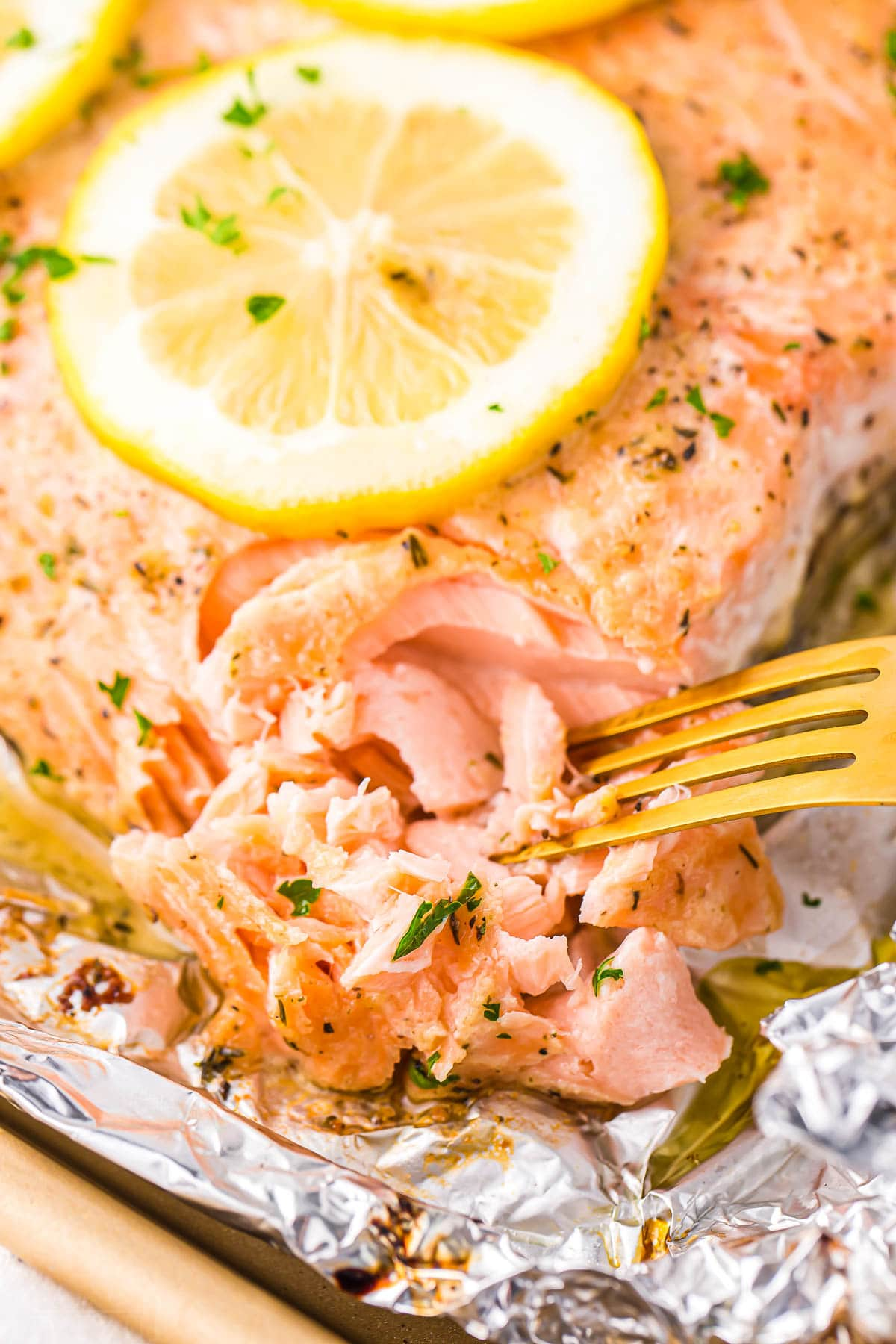 tender flaky salmon being flaked with a gold fork on a large salmon filet topped with a lemon slice.