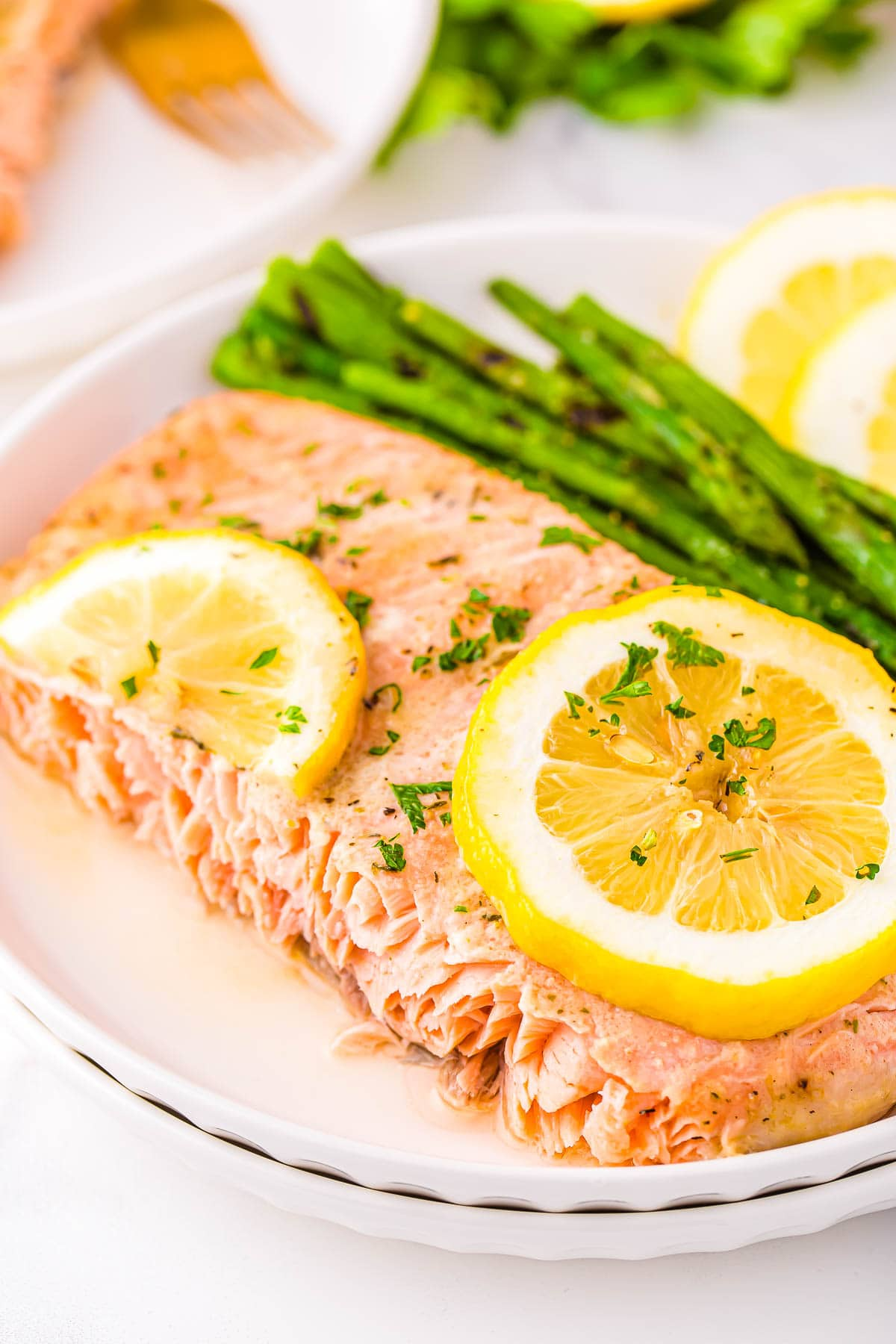 piece of baked salmon plated with asparagus and fresh lemon slices sitting on white plate.