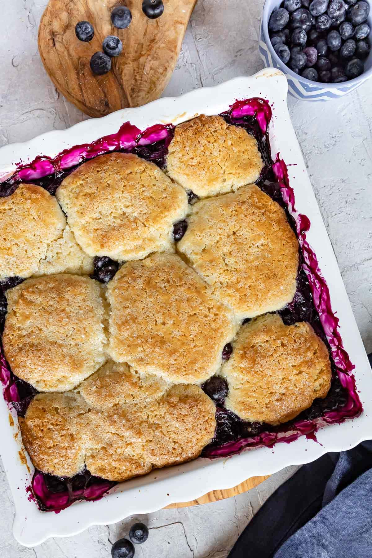 top down look at baked blueberry cobbler in white baking dish.