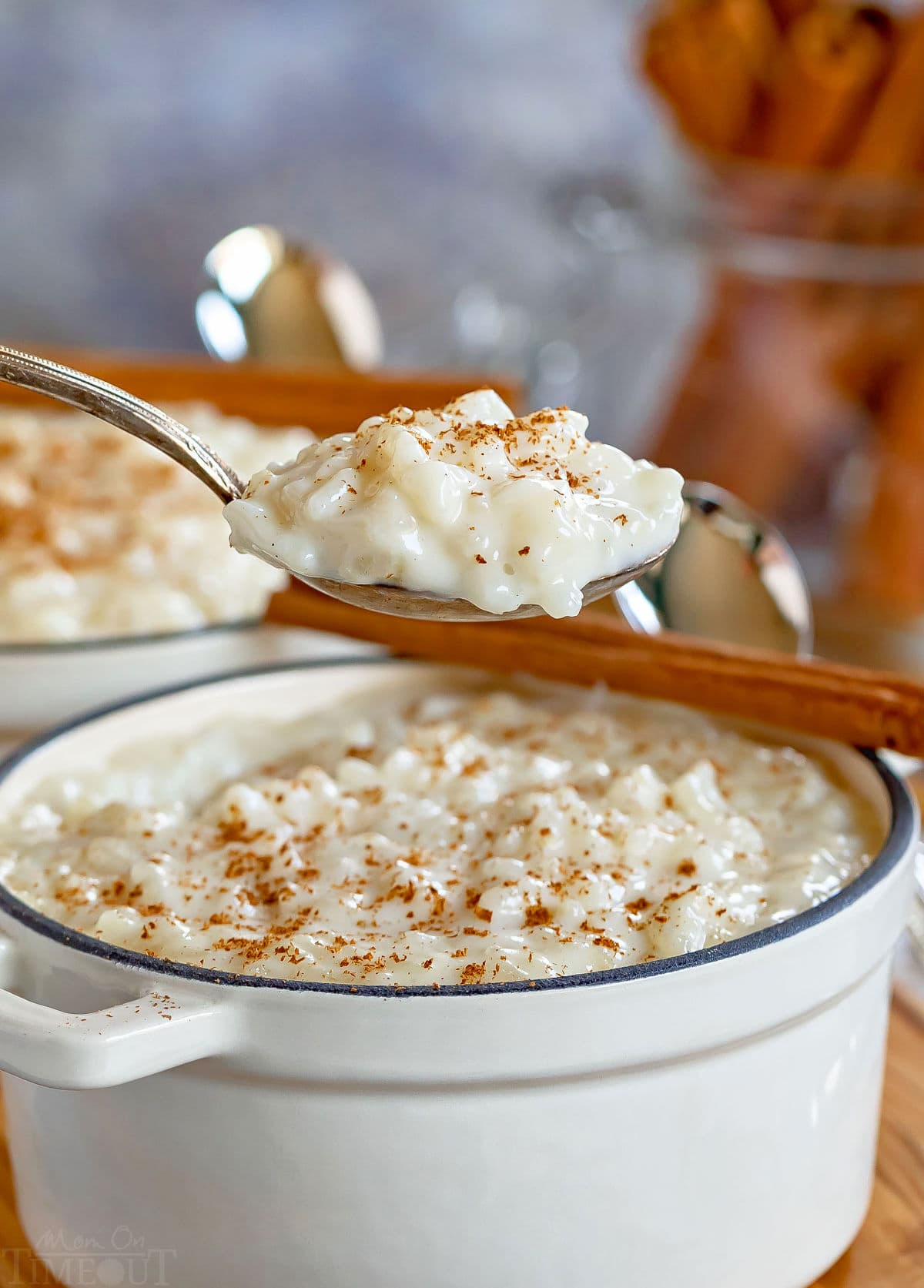 spoonful of rice pudding held up over the white pot it is being served from with freshly grated cinnamon stick on top.