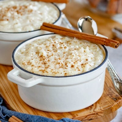 rice pudding served in 2 small white cast iron pots with cinnamon sticks resting on the rim.