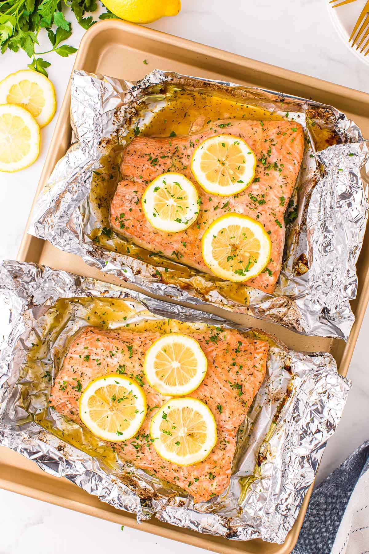 two large salmon filets baked in foil sitting on gold sheet pan topped with lemon slices and fresh minced parsley.