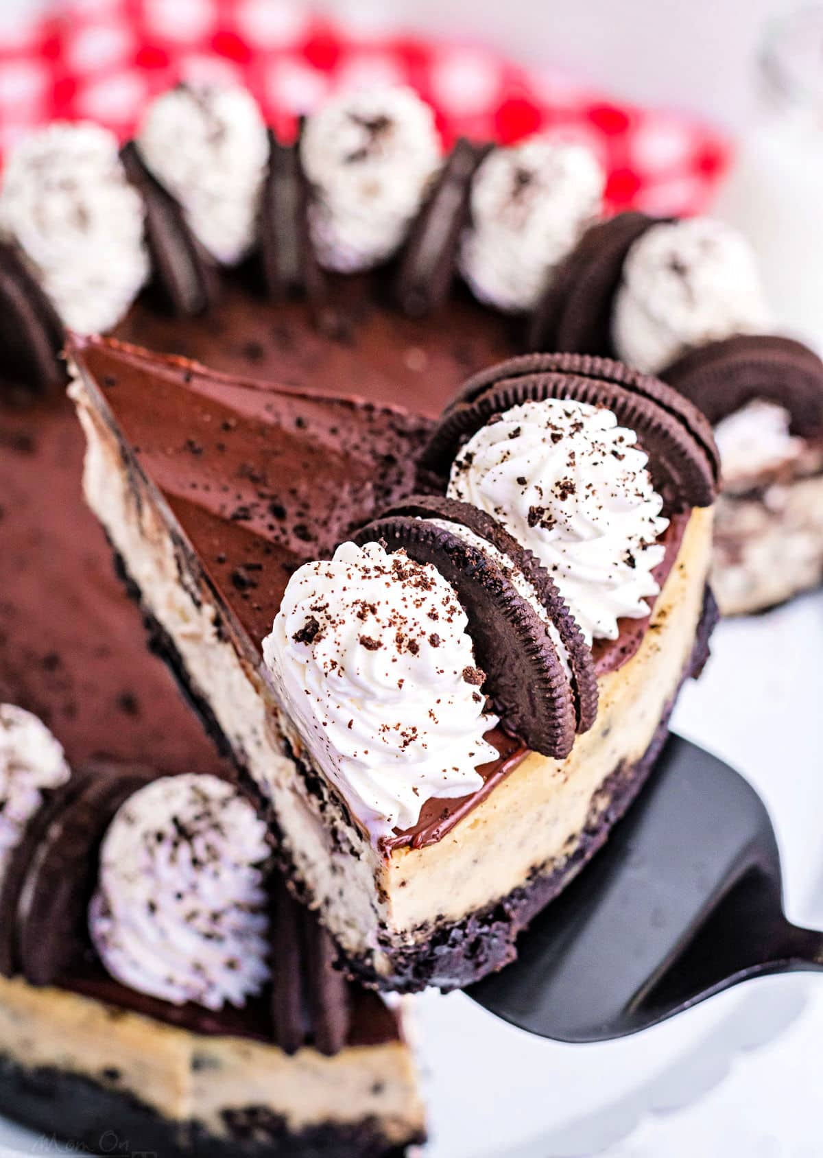 slice of oreo cheesecake being held above cake plate with rest of cheesecake.