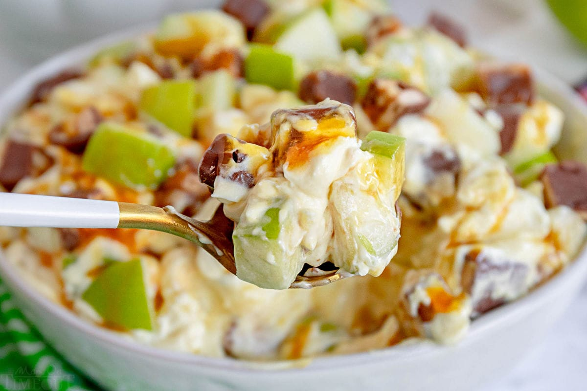 spoonful of caramel apple salad held in front of serving bowl.