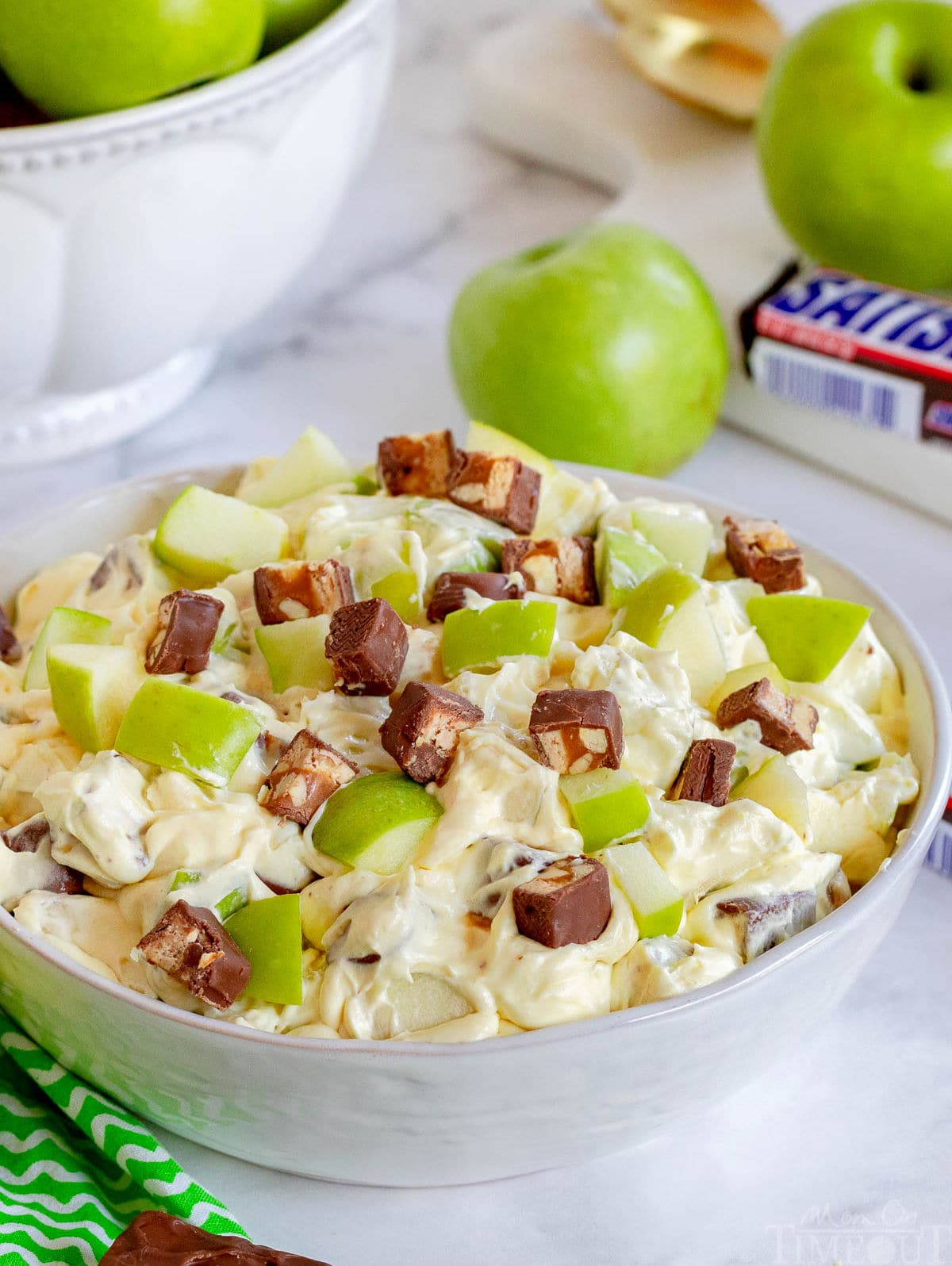 apple salad with snickers mixed in in large white bowl.
