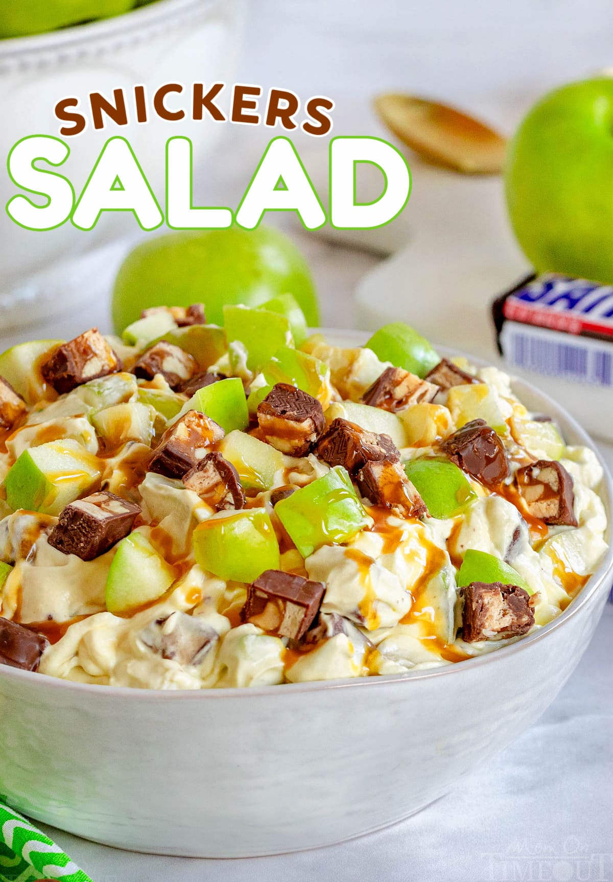 snickers salad in white salad bowl topped with a drizzle of caramel sauce. green apples and snickers candy bar in background. title overlay at top of image.