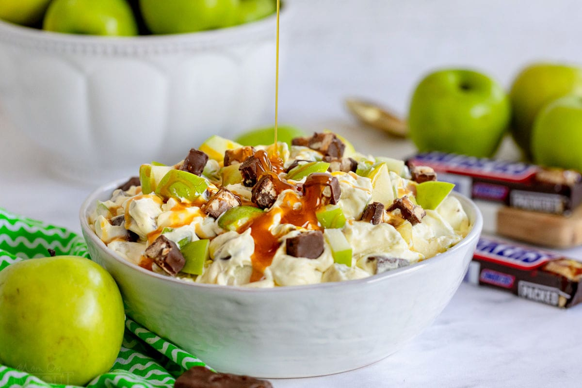 caramel sauce being drizzled over the top of the snickers salad in large white bowl. apples and snickers around the bowl.