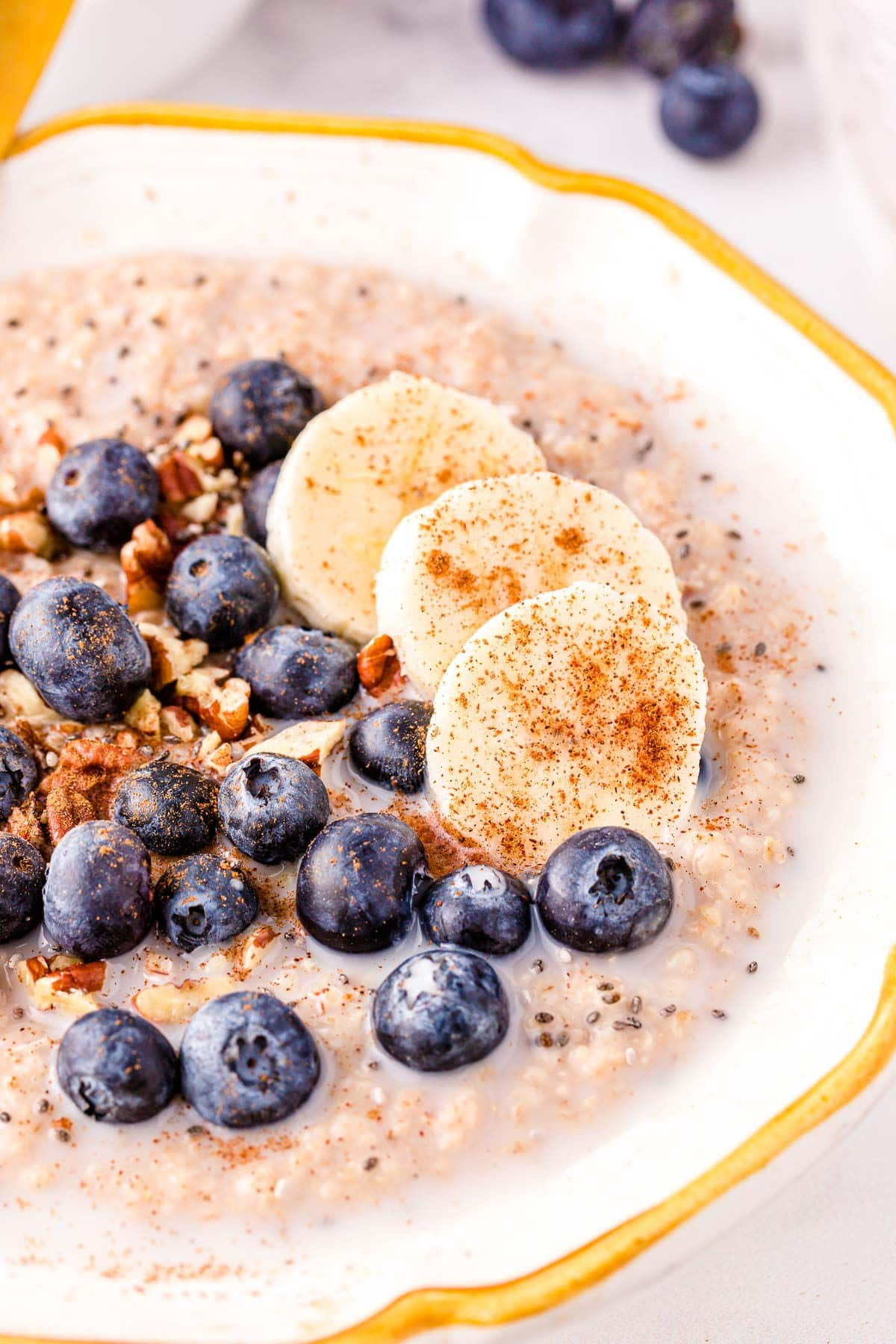close up look at steel cut oats in bowl topped with blueberries, banana slices and pecans.