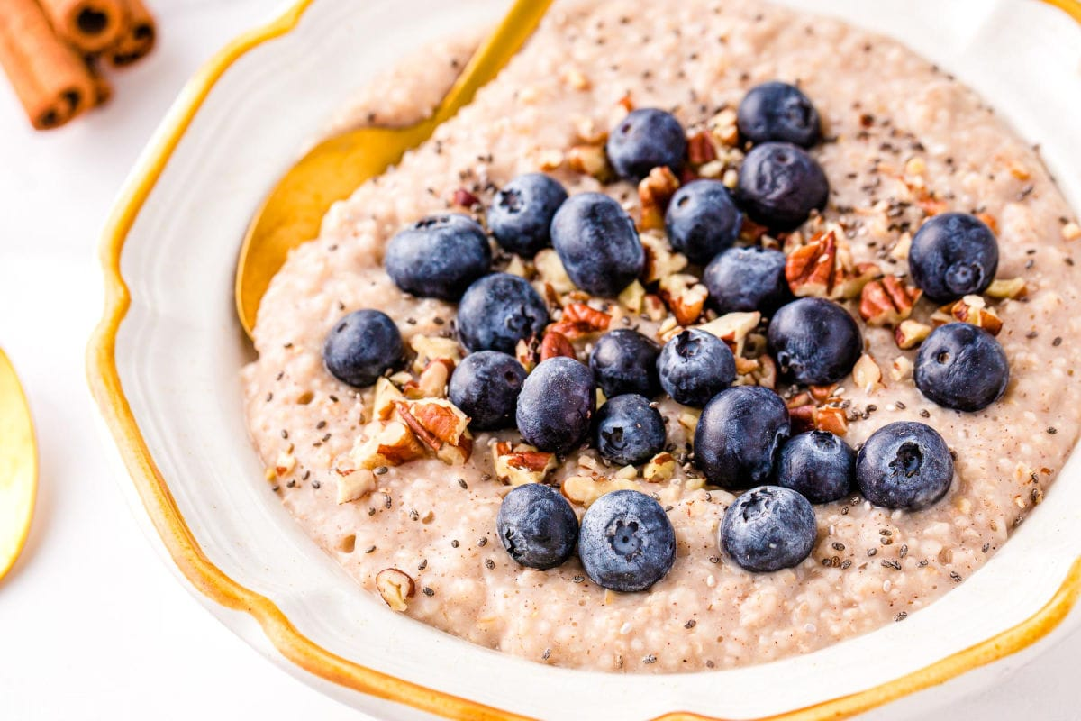steel cut oatmeal topped with blueberries, pecans and cinnamon in a white bowl with a gold spoon.