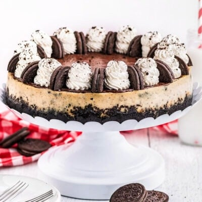 whole cheesecake made with oreos on a white metal cake stand and topped with whipped cream and oreo cookies.