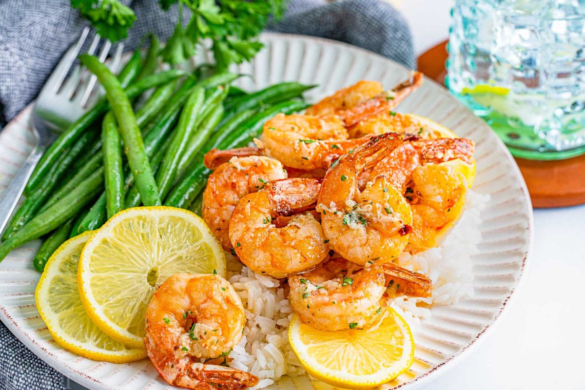 air fryer shrimp with garlic her butter sauce sitting on white scalloped edge plate with green beans and lemon slices.