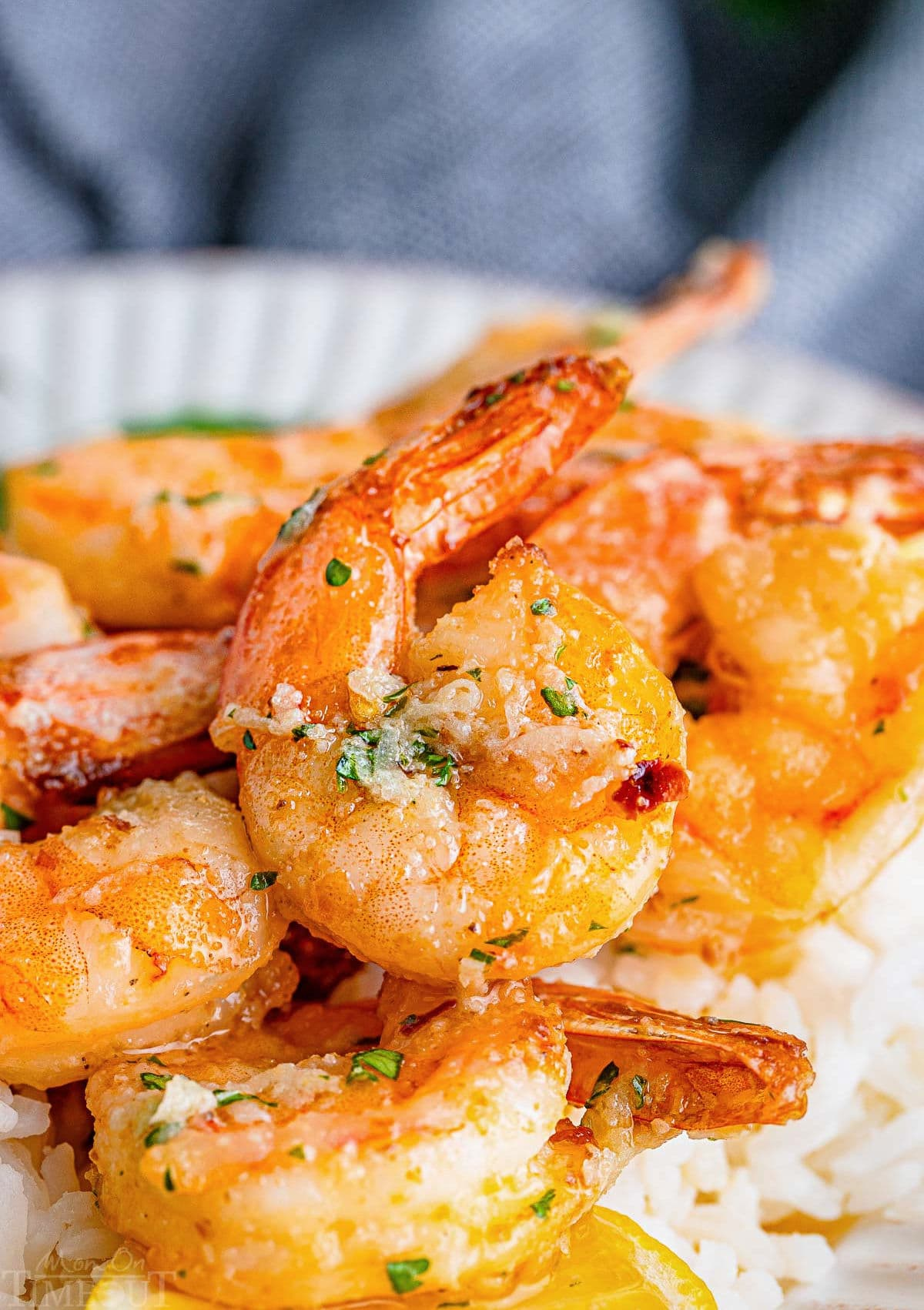 close up look at large shrimp cooked in air fryer topped with a garlic butter sauce sitting on a bed of white rice.