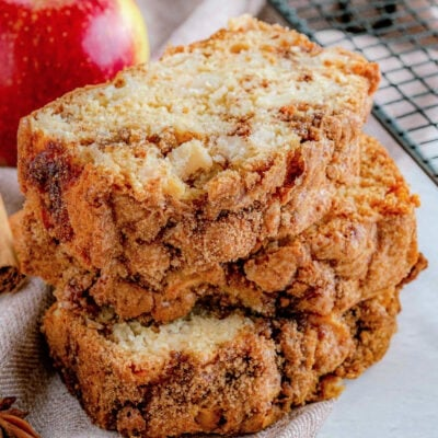 three slices of apple bread stacked next to a cooling rack with an whole red apple in background.