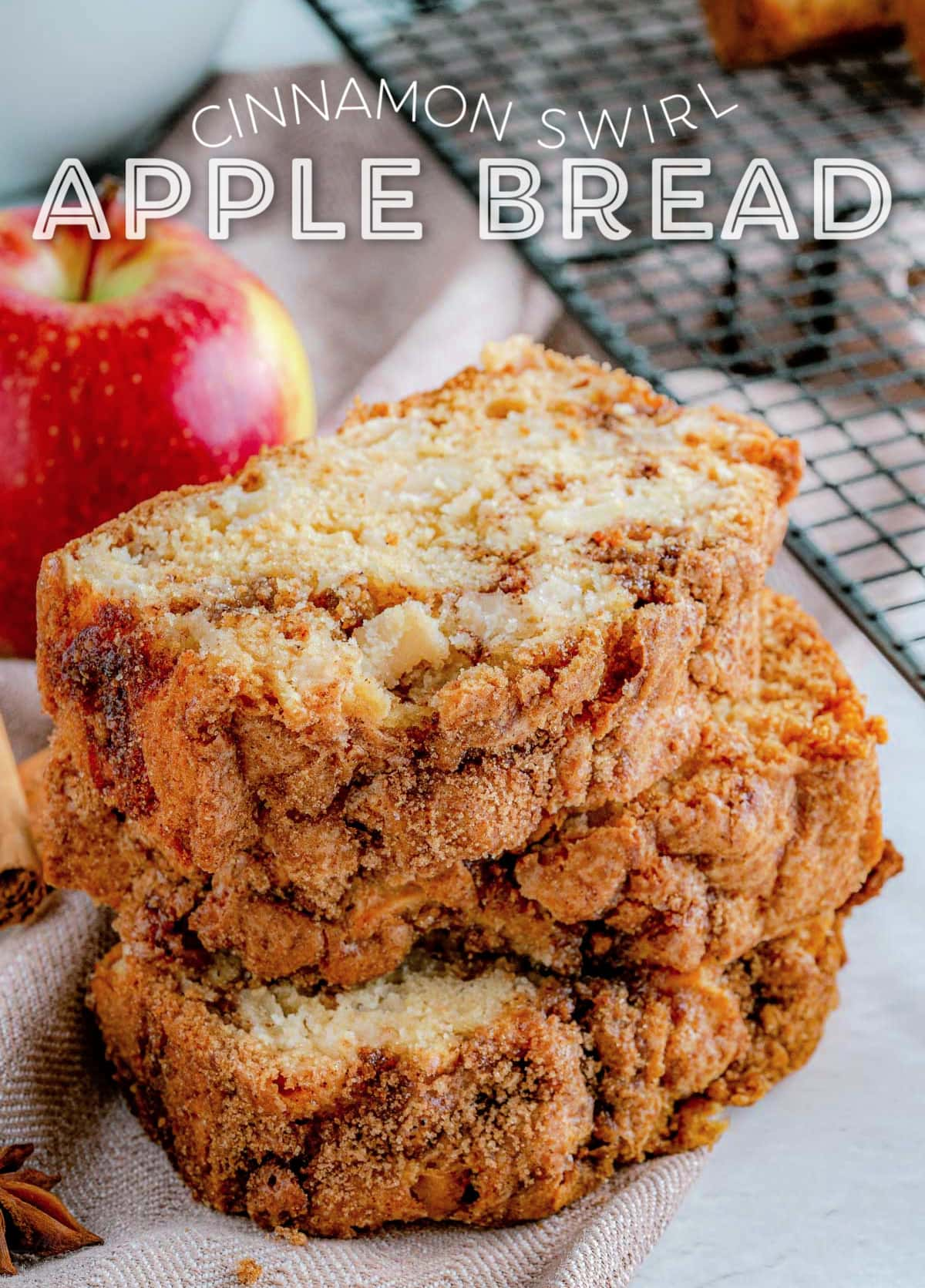 three slices of apple bread stacked next to a cooling rack with an whole red apple in background. title overlay at top of image.