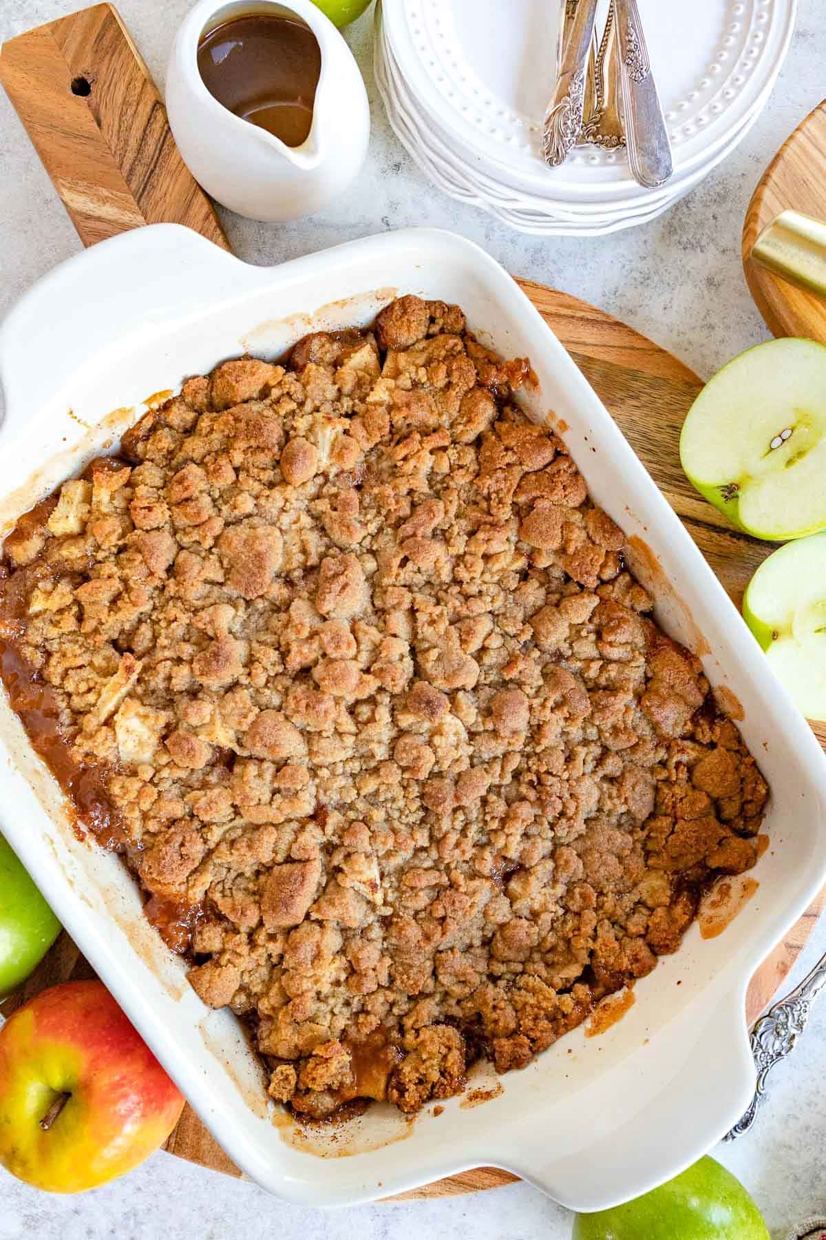 top down look at apple crumble in white baking dish sitting on wood cutting board.