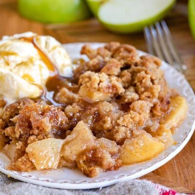 apple crumble served on a small white plate with vanilla ice cream and cut Granny Smith apples in background.