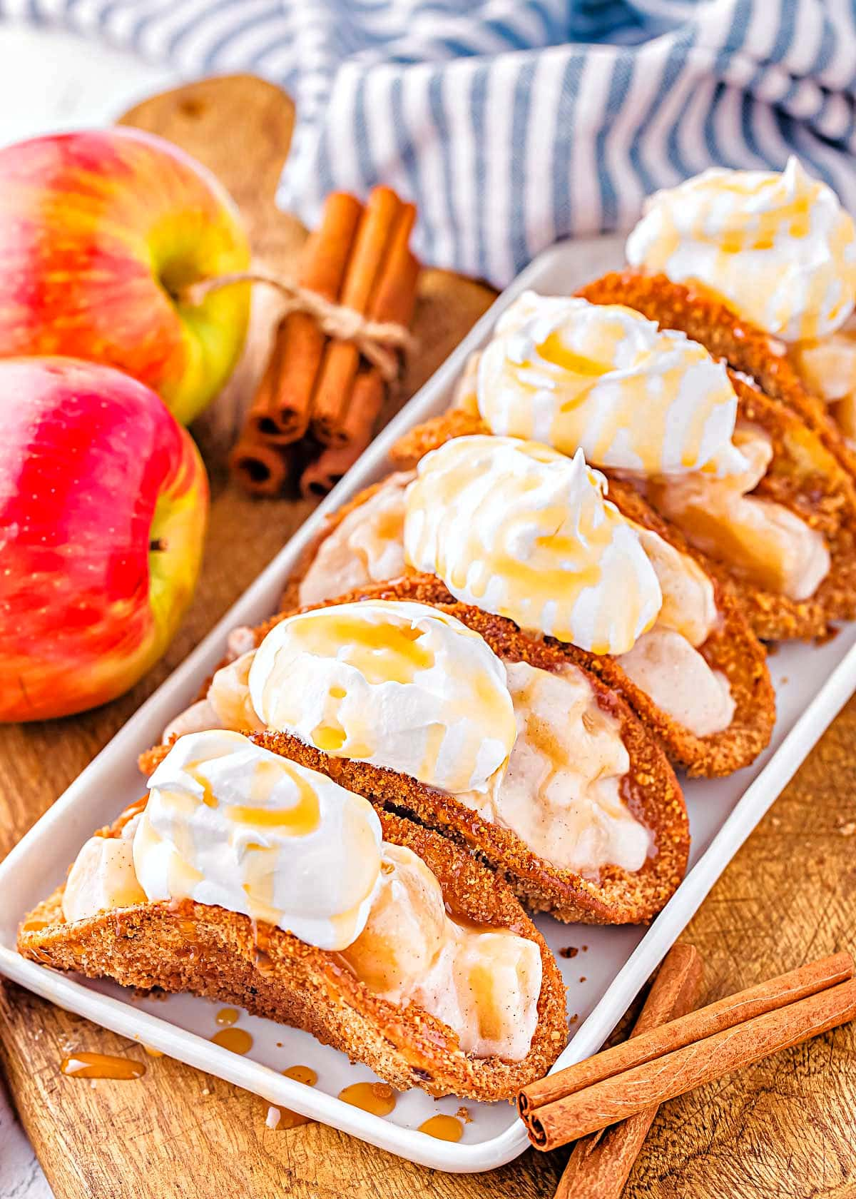 5 apple pie tacos on shallow white serving dish sitting next to blue and white striped napkin and fresh red apples.