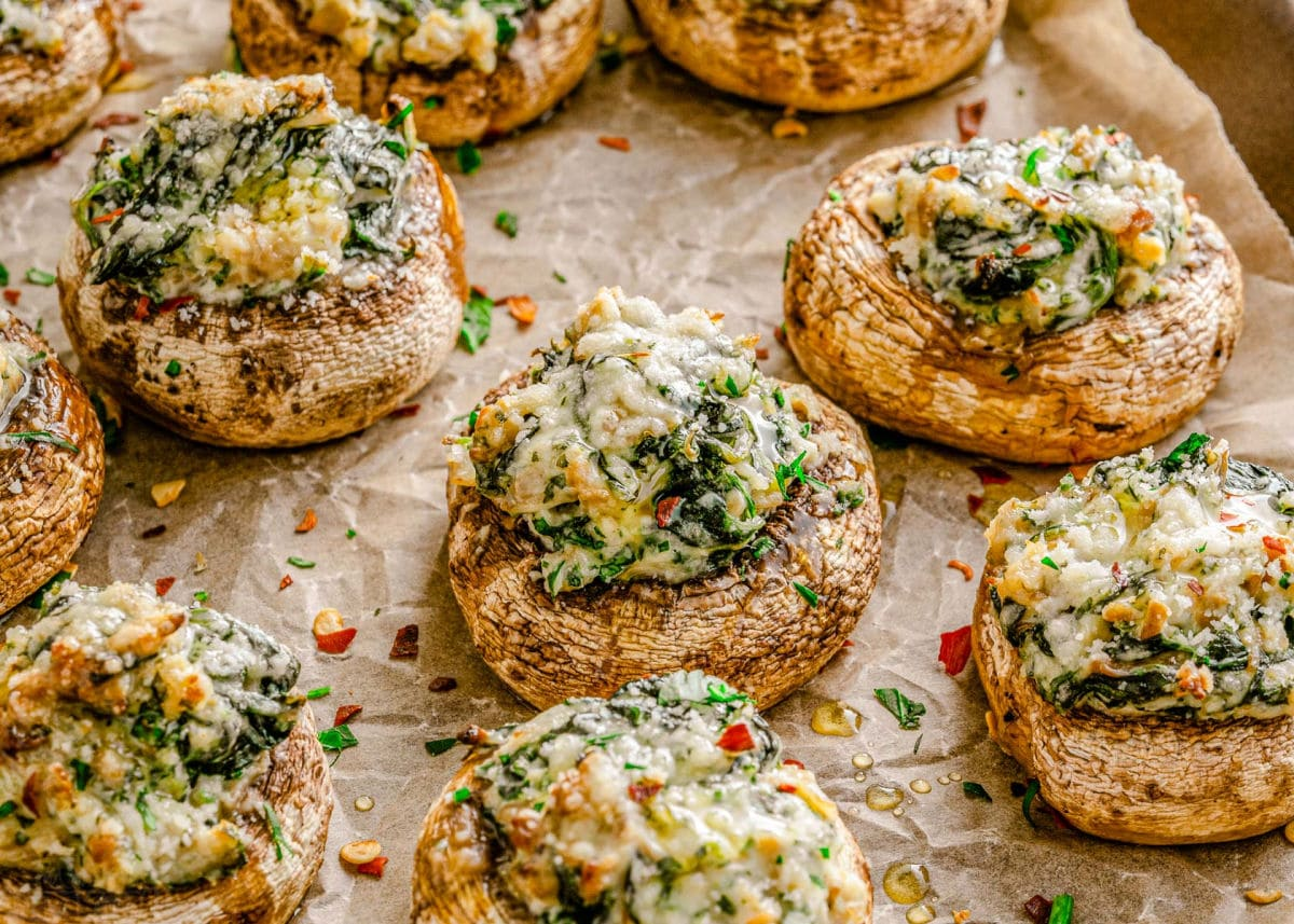 wide view of about 7 mushrooms stuffed with a creamy spinach filling and sprinkled with red pepper flakes and Parmesan cheese, ready to be enjoyed.