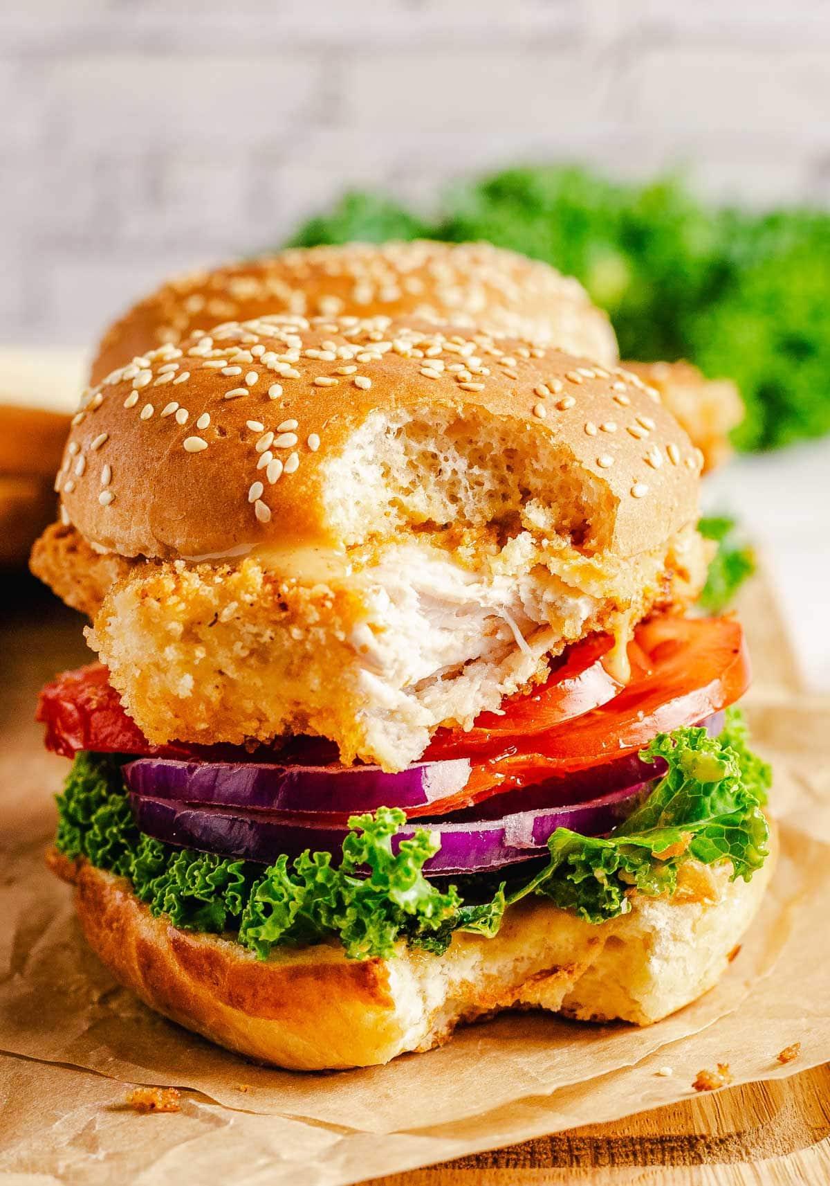 chicken sandwich with a big bite taken sitting on a brown parchment paper.