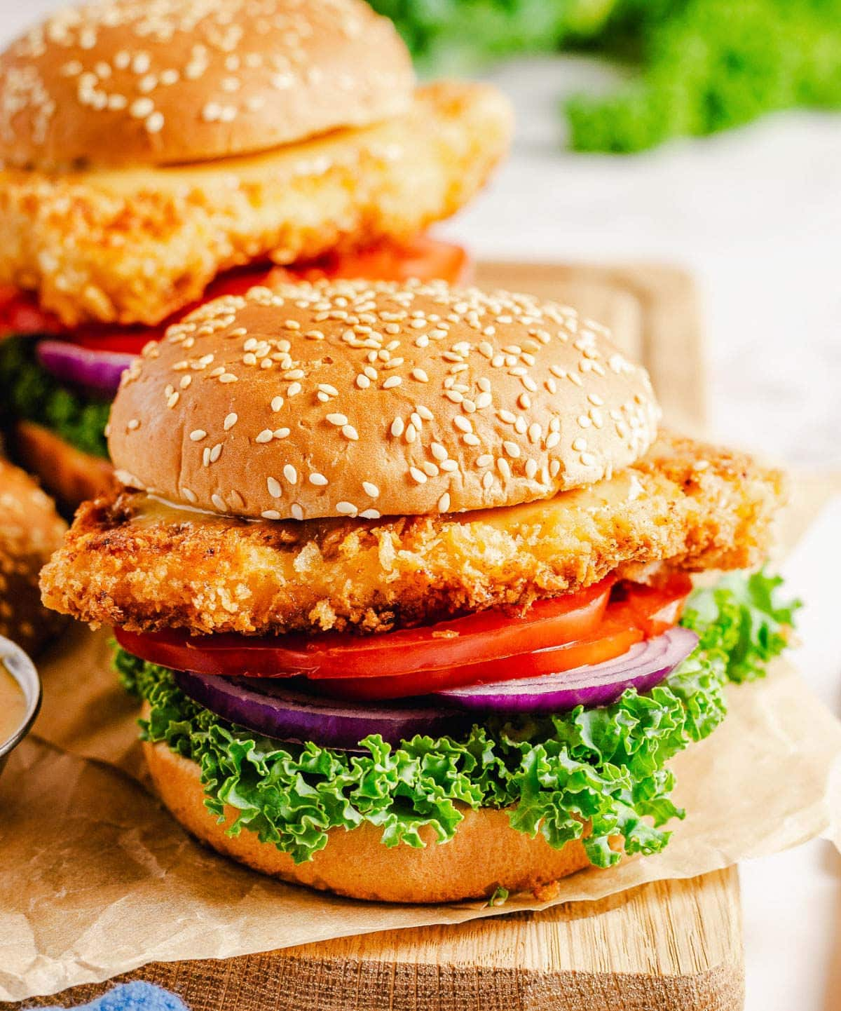 two chicken sandwiches on a wood board with all the fixins.