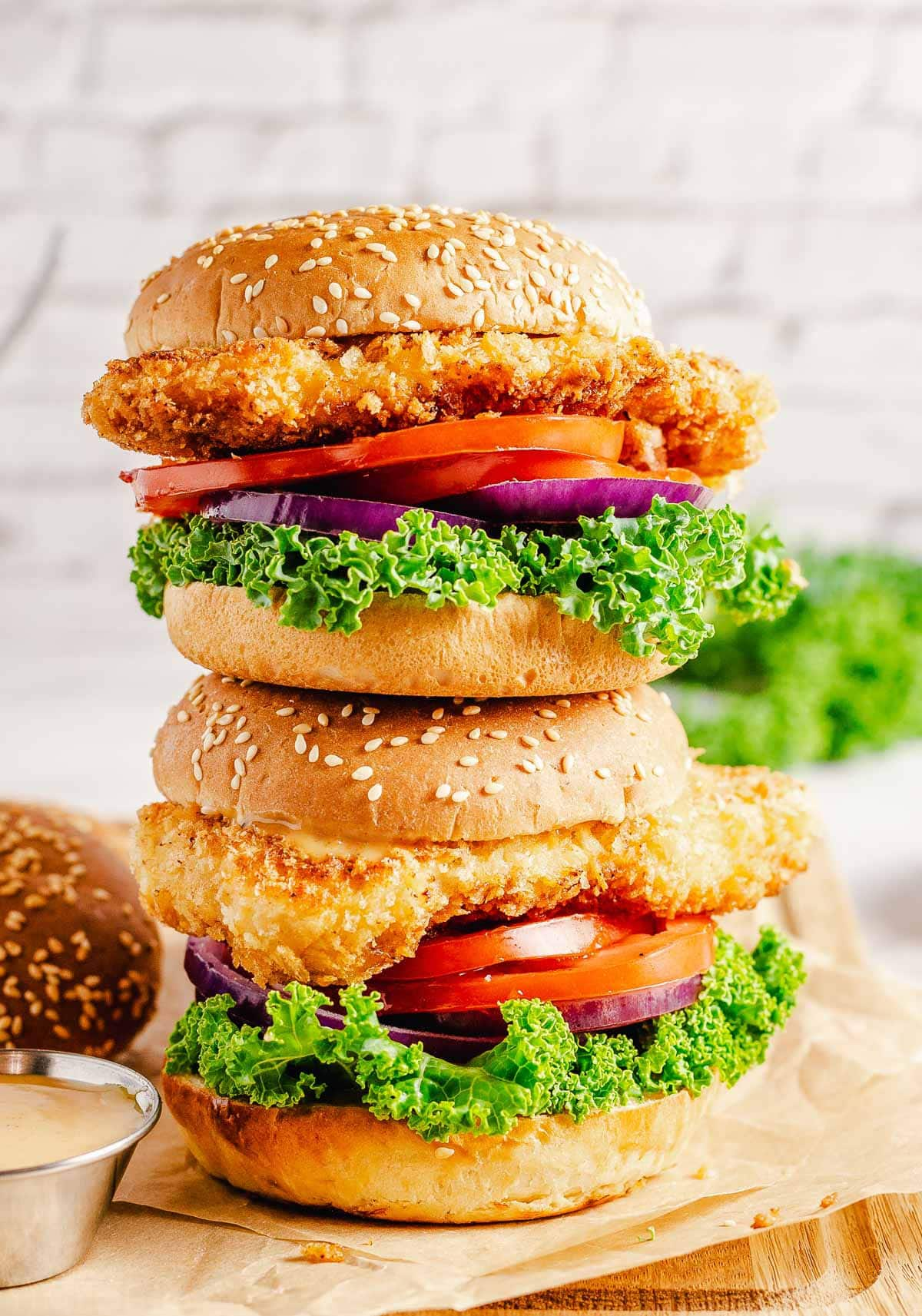 two chicken sandwiches stacked on each other sitting on wood cutting board.