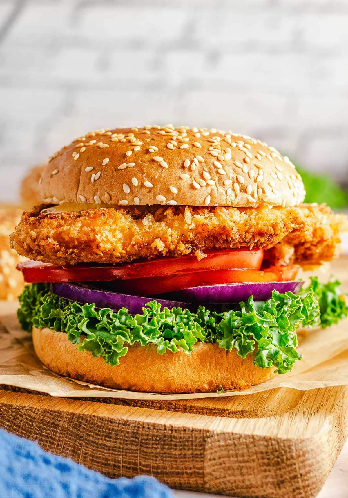 crispy chicken sandwich with all the topping on a seeded hamburger bun sitting on brown parchment on a wood cutting board.