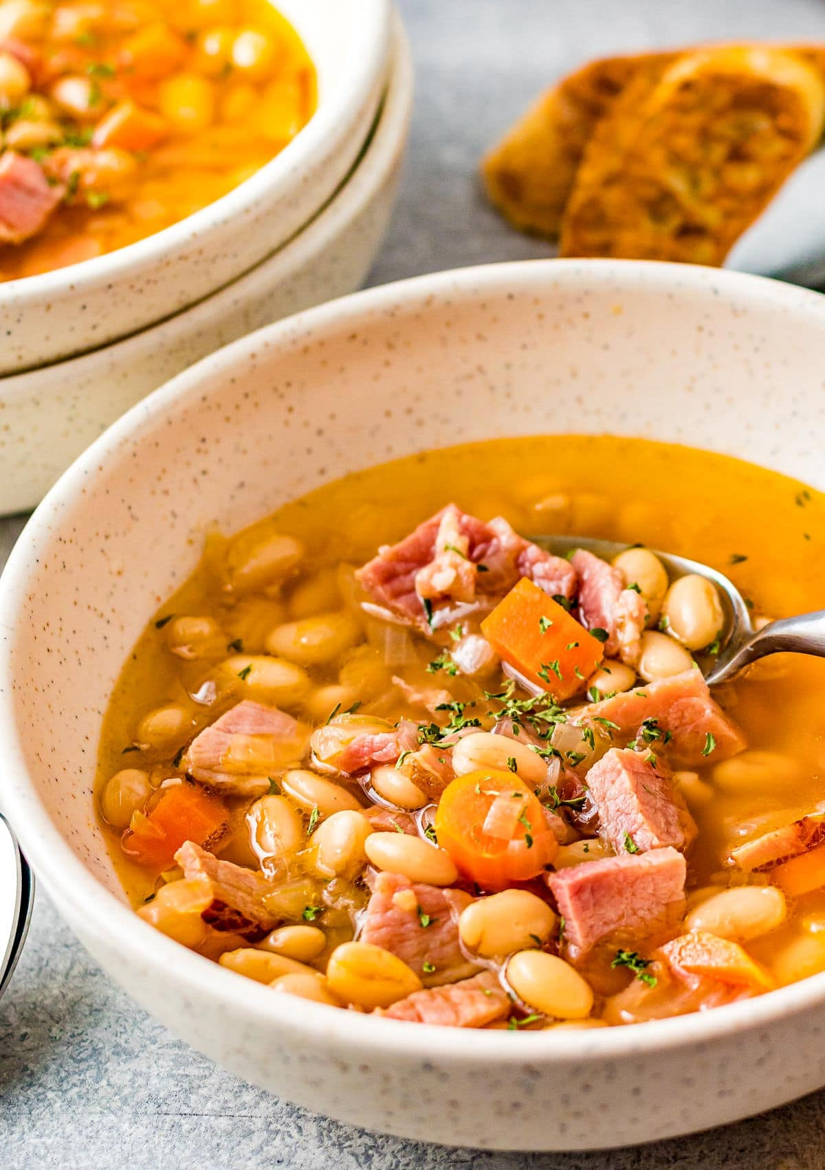 bowl full of ham and bean soup with lots of broth and a spoon.