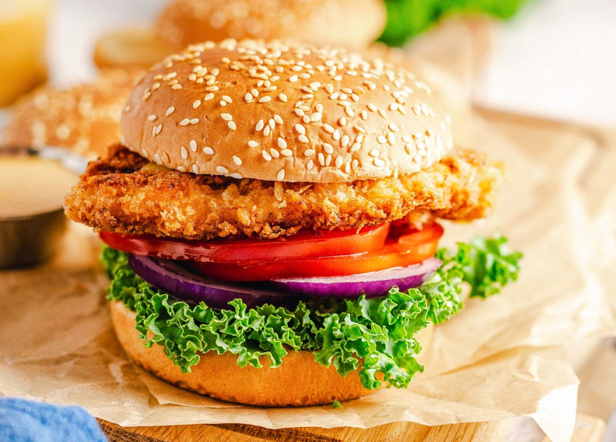 chicken sandwich with lettuce, red onion and tomato in a seeded bun.