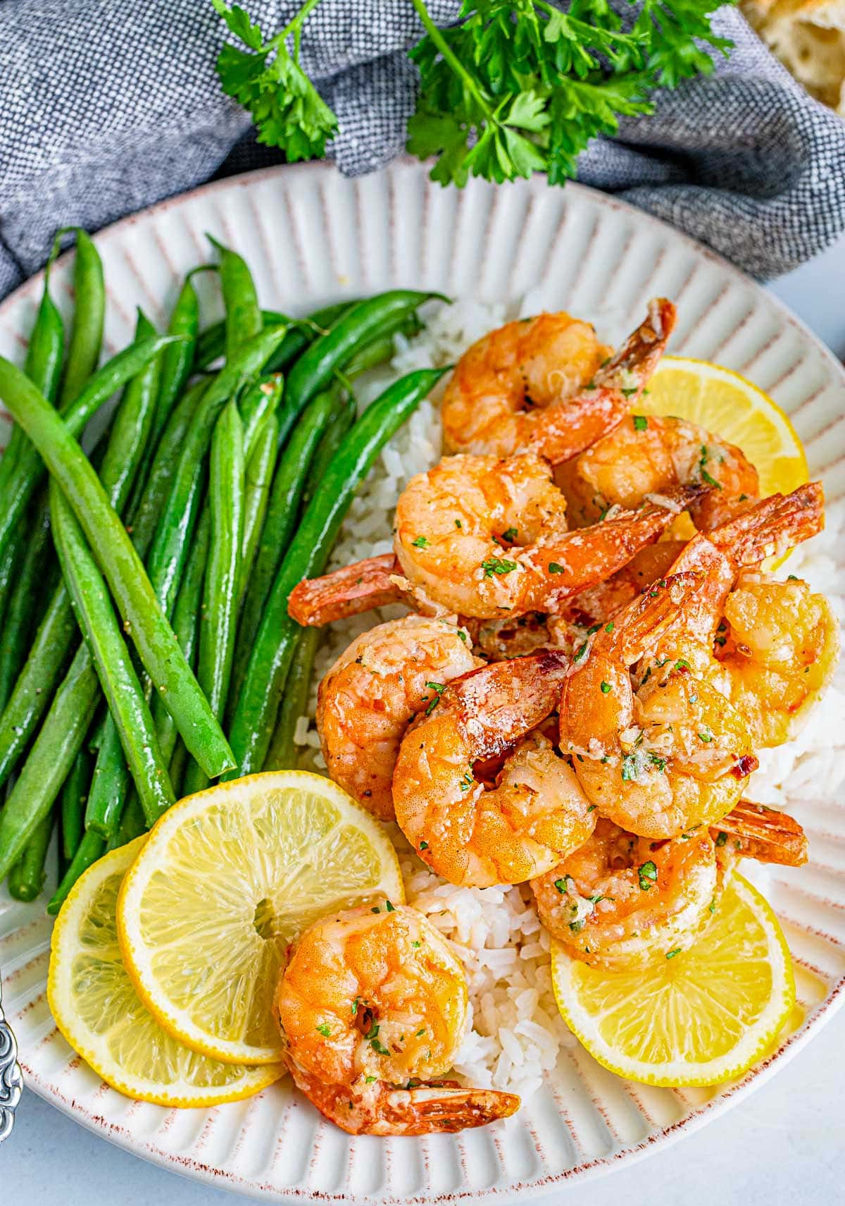 plate of air fryer shrimp topped with a garlic herb butter sauce.