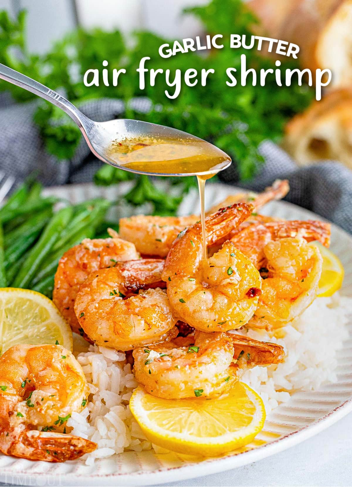 garlic her butter being drizzled on air fryer shrimp on a plate with green beans and lemon slices. title overlay at top of image.