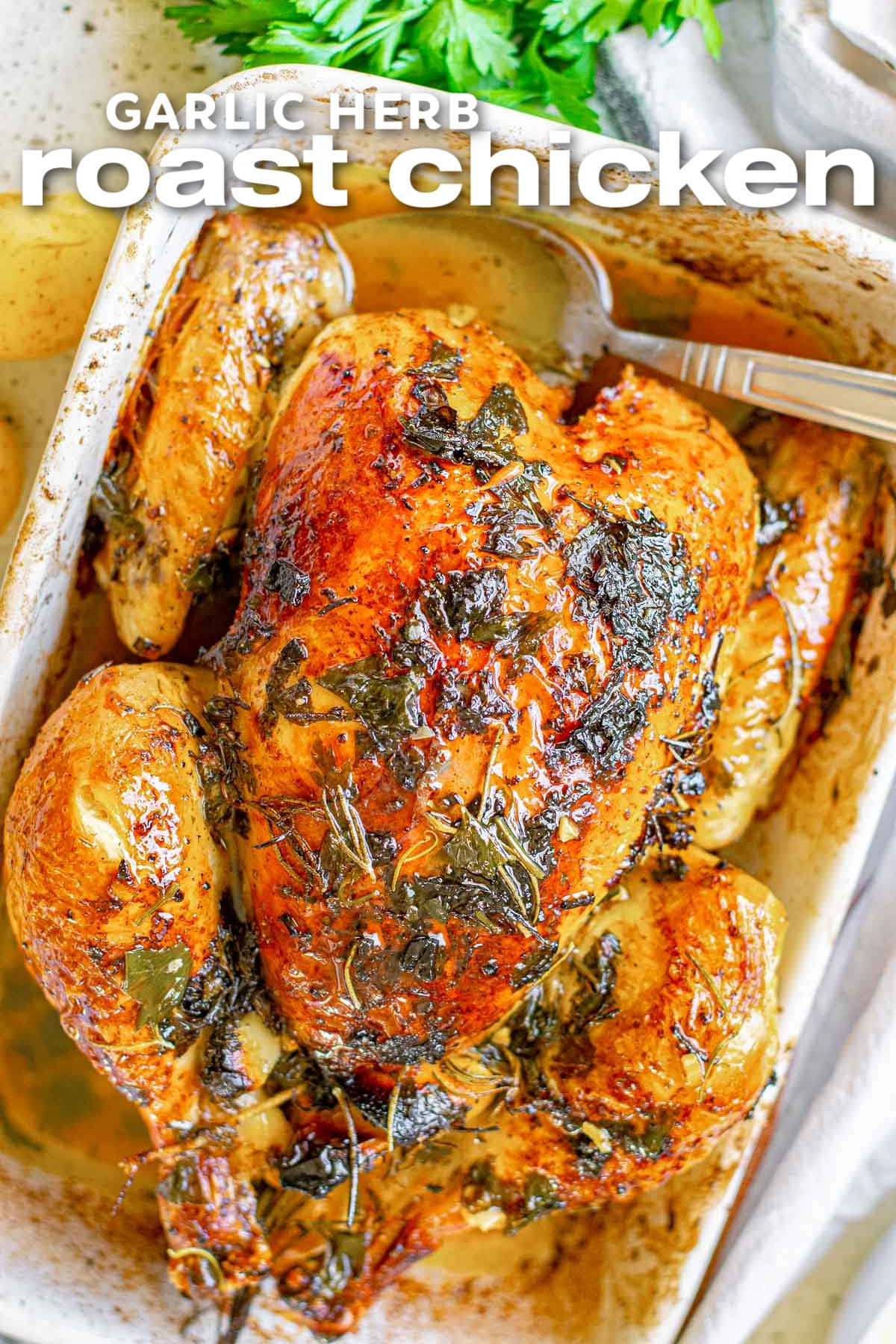 overhead look at roast chicken in white baking dish with crispy skin seasoned with fresh herbs. title at top of image.