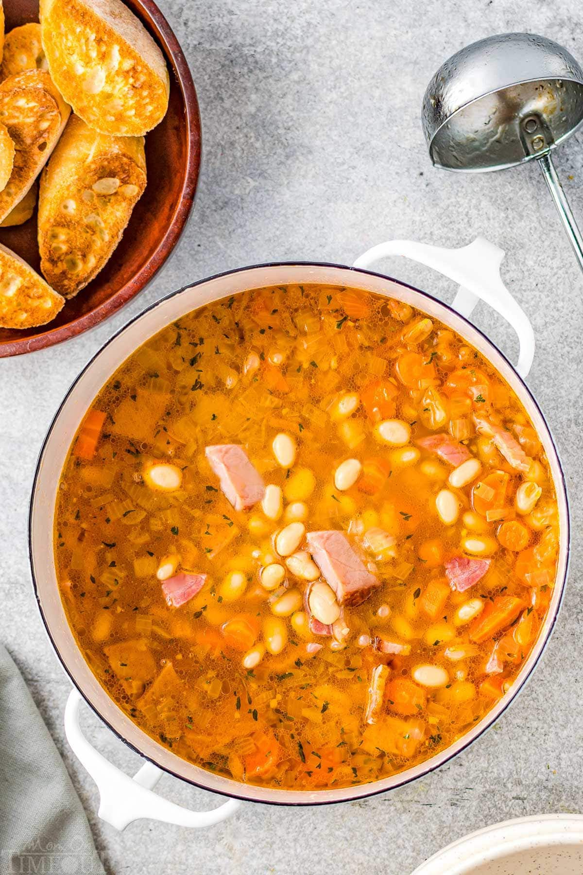 pot full of ham and bean soup with crusty bread in upper left corner on plate.