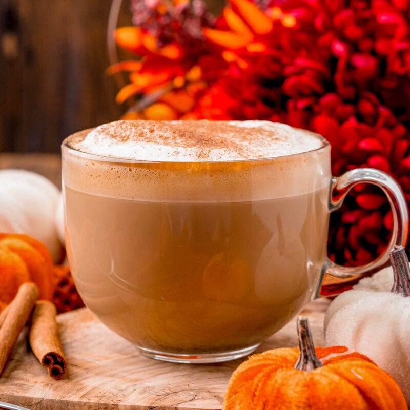 perfect mug of homemade pumpkin spice latte sitting olive board ready to be enjoyed.