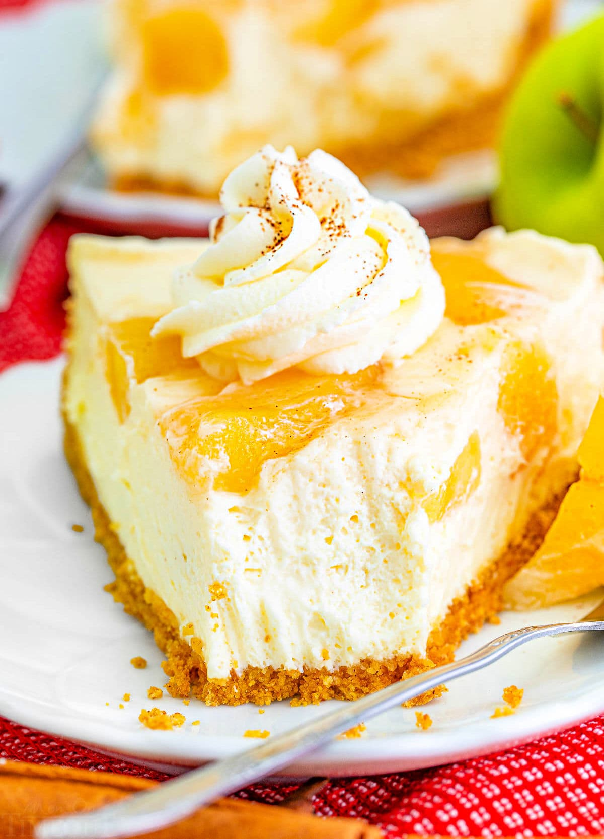 look at the creamy texture of this no bake apple cheesecake with a forkful removed from a slice.