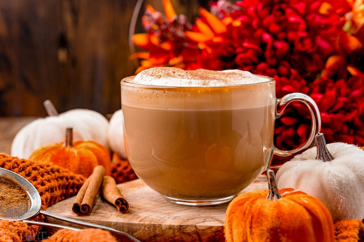 front view of a pumpkin spice latte ready to be enjoyed garnished with pumpkin pie spice and sitting in front of fall colored flowers on a wood board.