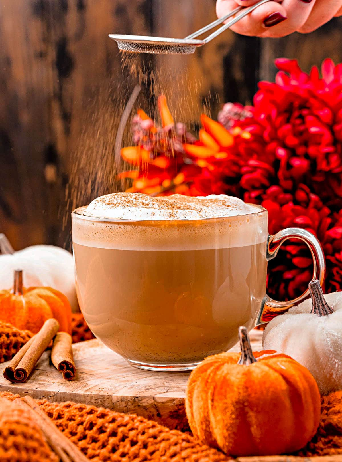 pumpkin spice latte in glass mug with pumpkin spice being dusted on top of the foam topping. colorful fall flowers in background and small velvet pumpkins scattered about.