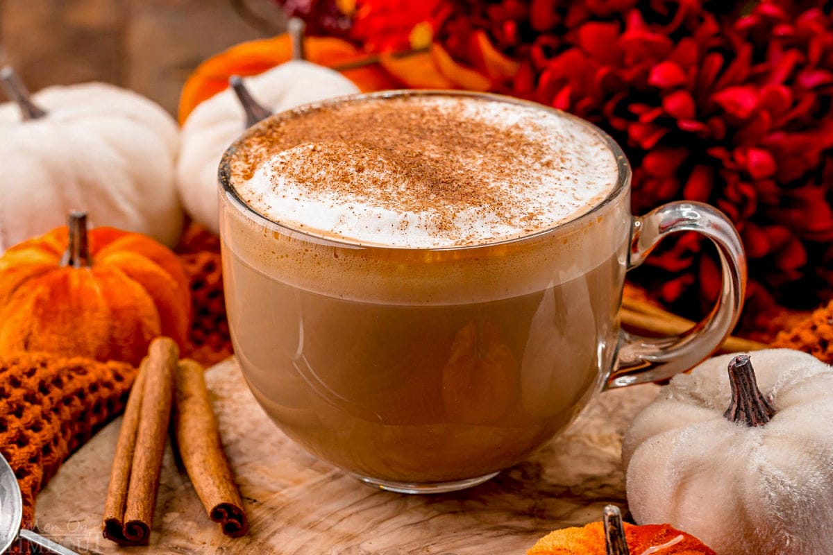 angled view of pumpkin spice latte so you can see the layers in the glass mug as well as the pumpkin pie spice topping.
