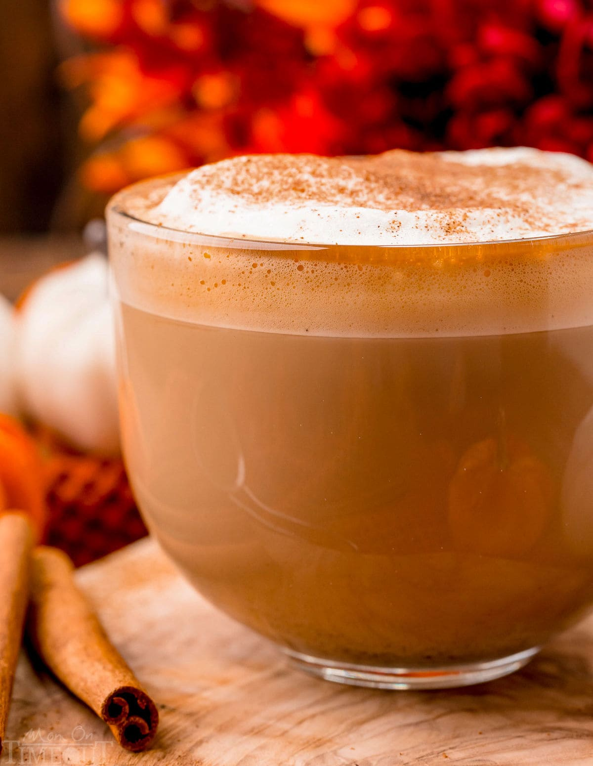 up close look at pumpkin spice latte made at home. Served in a glass mug and topped with frothed milk and pumpkin pie spice.