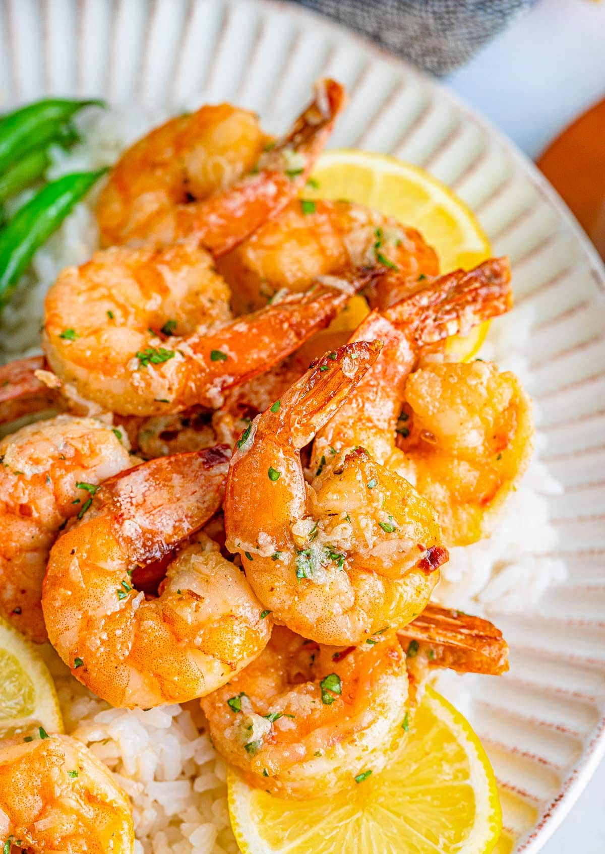 top down close up look at air fryer fried shrimp on a plate with lemon slices all topped with a garlic butter sauce.