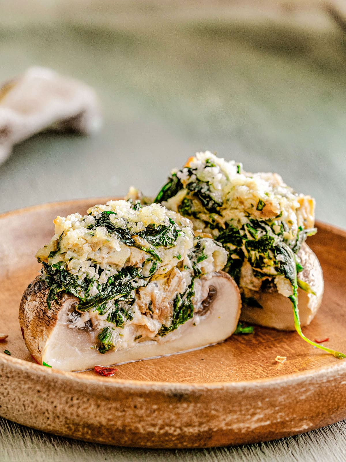 a stuffed mushroom split in half on a brown plate so you can see the creamy spinach filling.