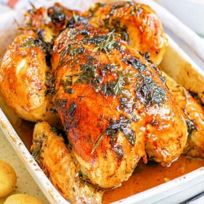 roasted chicken with golden skin and herbs cooked on top sitting in white roasting dish.