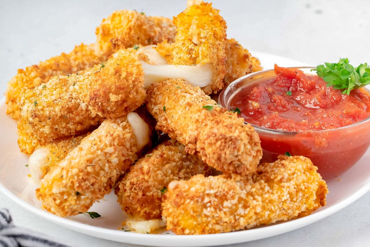 lots of mozzarella sticks cooked int he air fryer sitting on white plate with small bowl of marinara sauce.