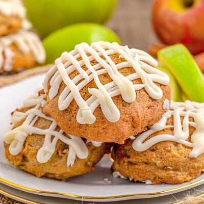 apple cookies sitting on white plate with gold rim with maple icing drizzle don top. fresh apples and apple slices in background.