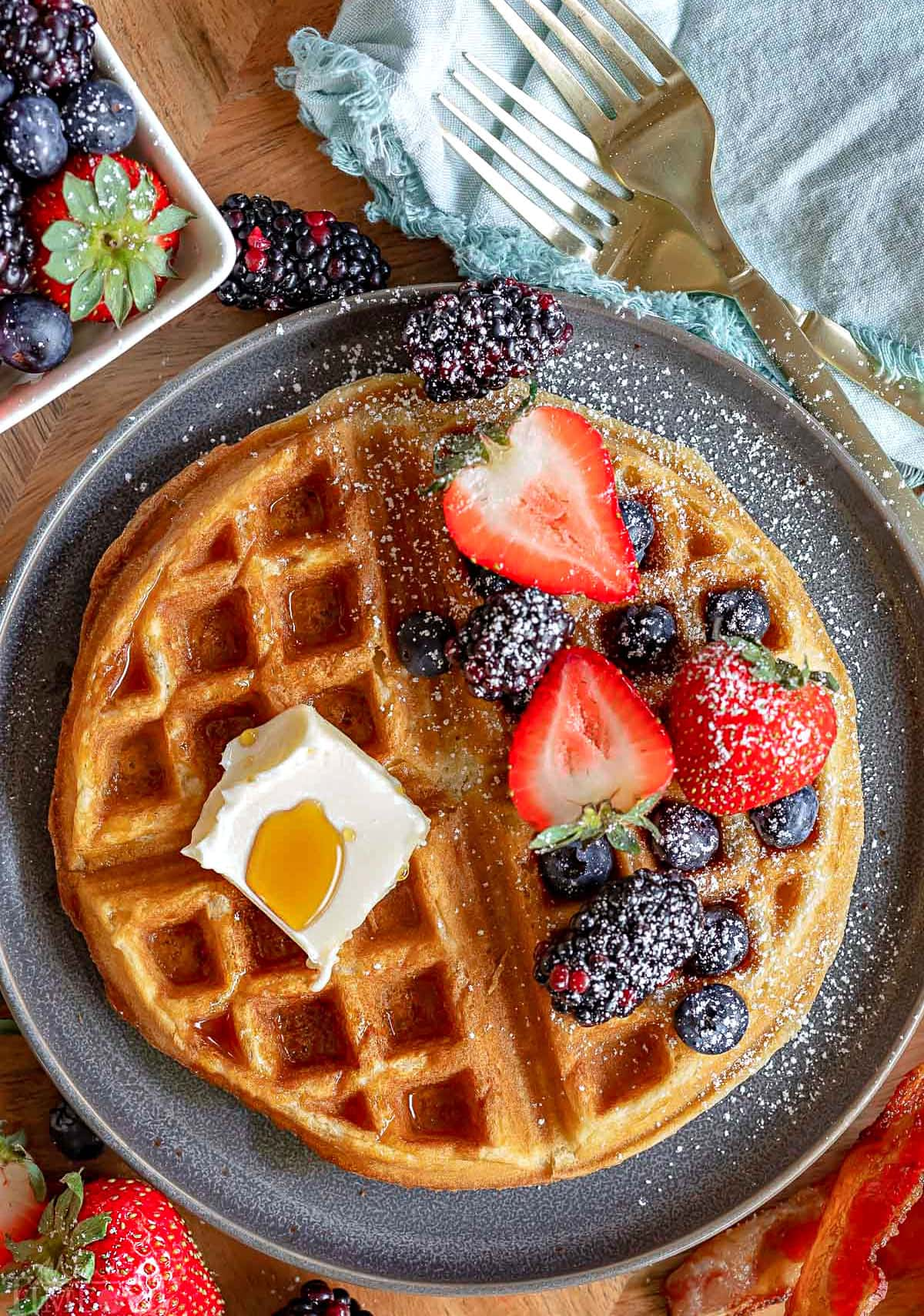 top down view of gray plate with one waffle. Half of the waffle topped with butter and syrup and half topped with berries and powdered sugar.